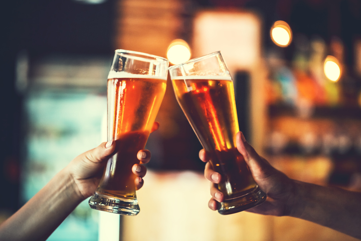 two friends toasting with glasses of beer