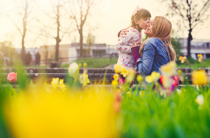 mother and daughter outside surrounded by tulips